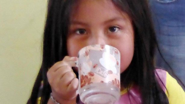 Girl drinking clean water in Ecuador provided by Project M:25