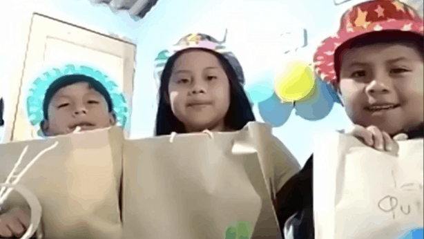 Kids smiling to camera with paper bags